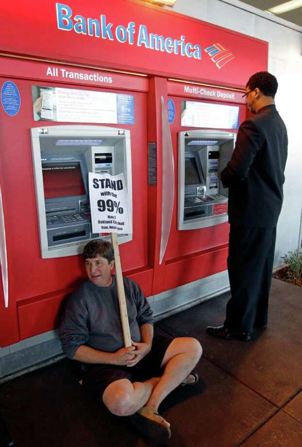 "FILE - In this Nov. 2, 2011 file photo, a protesters sits in front of an ATM machine as a customer gets money at a Bank of America branch in Oakland, Calif. The spirit behind ""Bank Transfer Day"" caught fire with the Occupy Wall Street protests around the country and had more than 77,000 supporters on its Facebook page as of Friday. The movement has already helped beat back Bank of America's plan to start charging a $5 debit card fee.  (AP Photo/Paul Sakuma, File) Photo: Paul Sakuma"