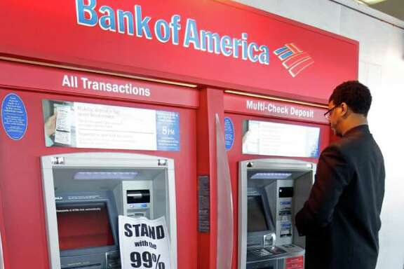 "FILE - In this Nov. 2, 2011 file photo, a protesters sits in front of an ATM machine as a customer gets money at a Bank of America branch in Oakland, Calif. The spirit behind ""Bank Transfer Day"" caught fire with the Occupy Wall Street protests around the country and had more than 77,000 supporters on its Facebook page as of Friday. The movement has already helped beat back Bank of America's plan to start charging a $5 debit card fee.  (AP Photo/Paul Sakuma, File)"