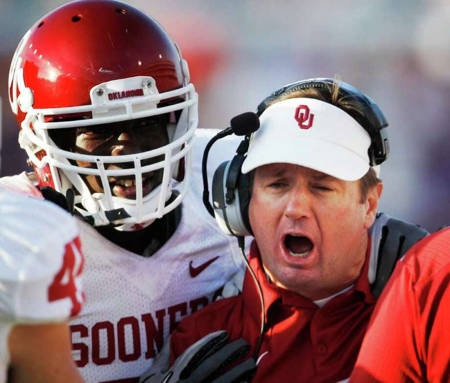 Oklahoma coach Bob Stoops instructs his team as defensive back Sam Proctor, left, listens in during the second half of an NCAA college football game against Kansas State Saturday, Oct. 29, 2011, in Manhattan, Kan. Photo: AP