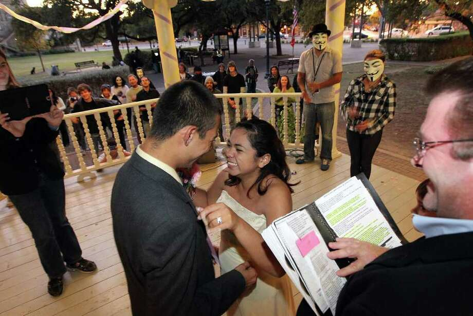 The Occupy SA movement held a wedding of two participants at HemisFair Plaza on Friday, Nov. 4, 2011. The couple Victoria Saucedo (center right) and Kristian Rodriguez tied the knot on Friday as several other Occupy SA protestors watched the ceremony take place. The Occupy protest in San Antonio is entering near the one-month mark and despite reports of arrests of protesters, this group has remained reasonably peaceful. Kin Man Hui/kmhui@express-news.net Photo: Kin Man Hui, SAN ANTONIO EXPRESS-NEWS / San Antonio Express-News