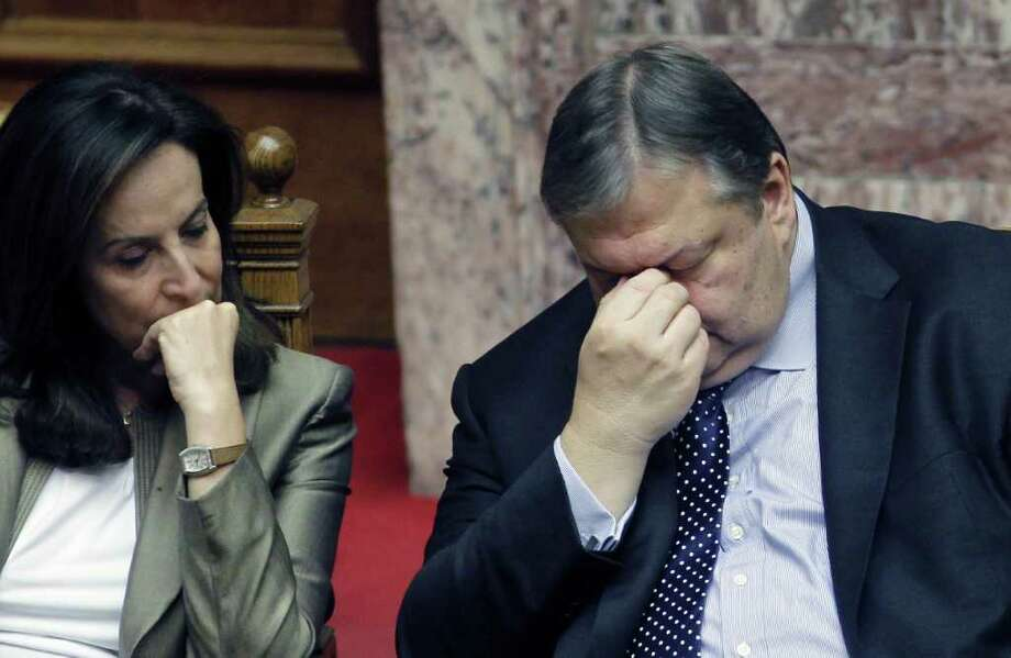 PETROS GIANNAKOURIS: ASSOCIATED PRESS CONFIDENCE, BARELY: Greek finance minister Evangelos Venizelos, right, and education minister Anna Diamadopoulou reflect the tension before Saturday's vote for Prime Minister George Panpandreou as the economic crisis continues. Photo: Petros Giannakouris / AP