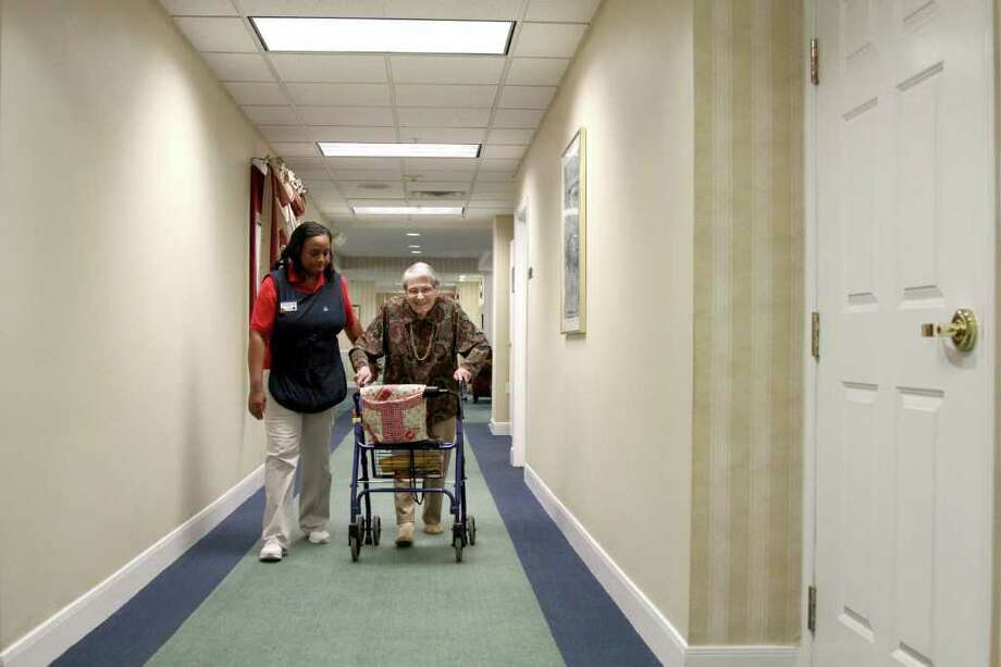 THOMAS B. SHEA : FOR THE CHRONICLE PERSONAL ATTENTION: Rhonda Davis, who's been with Atria for six years, helps  101-year-old Ellen Hunt at Atria's Sugar Land location. Photo: For The Chronicle:  Thomas B. Sh
