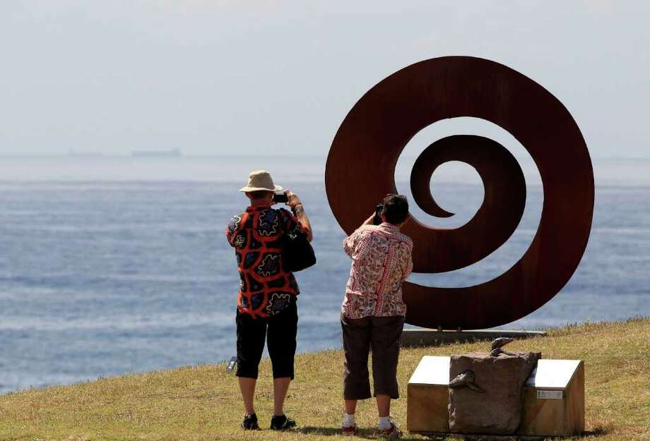 "A couple photograph an installation titled ""Ammonite 2006"" by artist Bert Flugelman that is part of the annual Sculpture by the Sea exhibition in Sydney, Friday, Nov. 4, 2011. Photo: Rick Rycroft, Associated Press / AP"