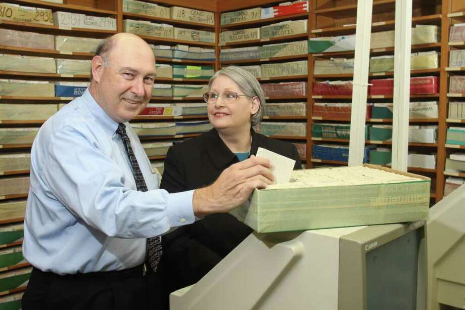 (For the Chronicle/Gary Fountain, October 14, 2011) Marian and Paul Cones of CourthouseDirect.com, with deed record documents that are on microfilm. These documents have been scanned to electronic format, but they keep the source documents and occasionally need to refer to them. Photo: Gary Fountain / Copyright 2011 Gary Fountain