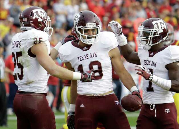 Texas A&M tight end Michael Lamothe, center, celebrates with teammates Ryan Swope, left, and Uzoma Nwachukwu after catching a touchdown pass during the first half of an NCAA college football game against Iowa State, Saturday, Oct. 22, 2011, in Ames, Iowa. Photo: AP