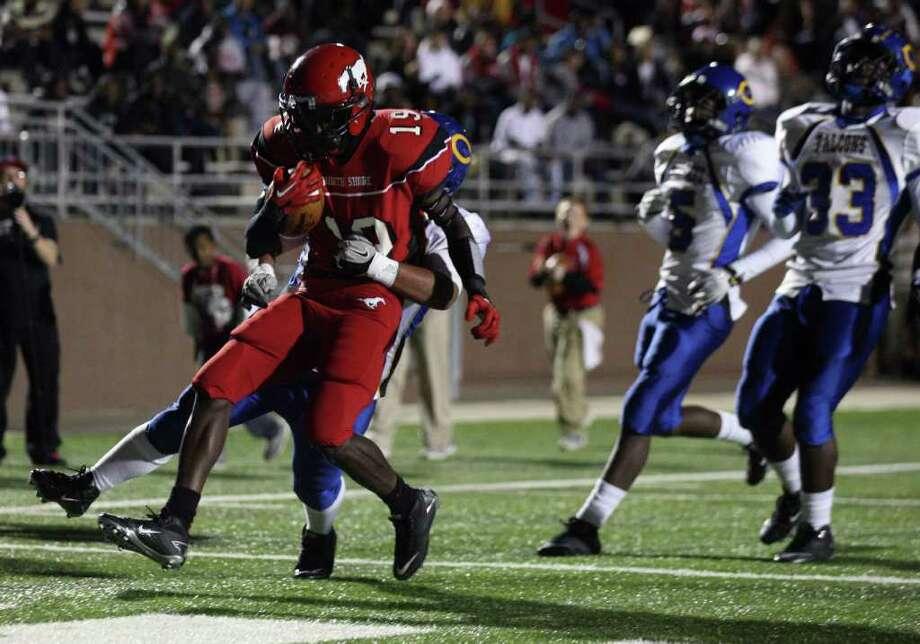North Shore 45, Channelview 26. North Shore's Larry McDuffey (19) carries Channelview's Jose Escobedo into the end zone for the Mustangs' first score of the game during the first half, Friday, November 4, 2011 at Galena Park Stadium in Houston. Photo: Eric Christian Smith, For The Chronicle