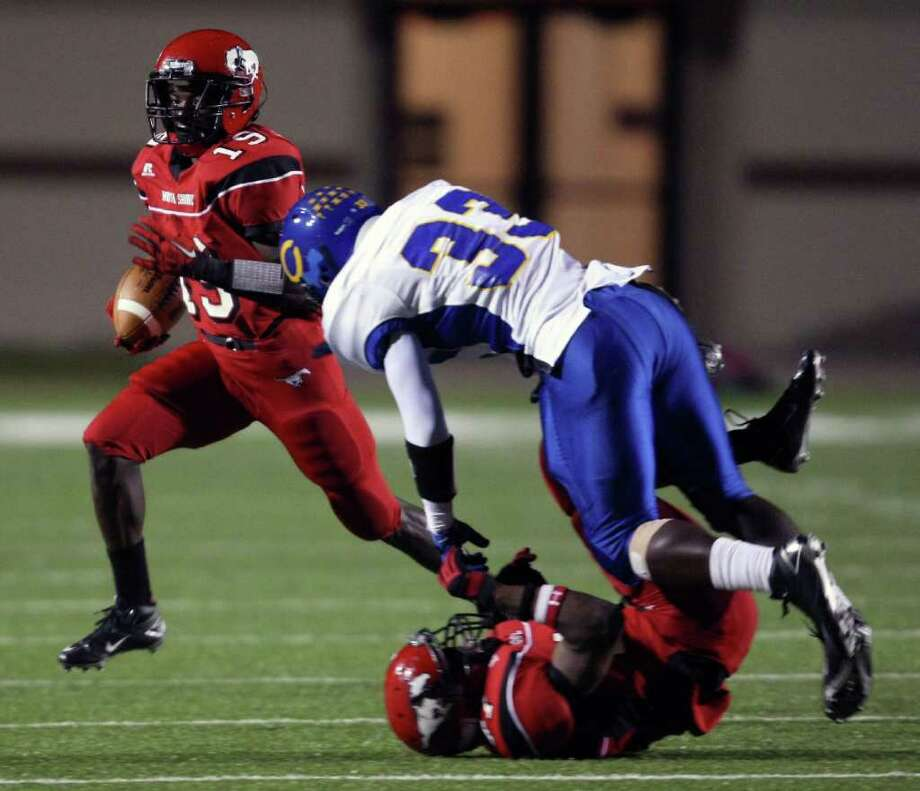 North Shore's Larry McDuffey (19) looks for extra yardage after a reception as Channelview's Dwain Taylor trips over a Mustang blocker during the first half of a District 21-5A high school football game, Friday, November 4, 2011 at Galena Park Stadium in Houston. Photo: Eric Christian Smith, For The Chronicle