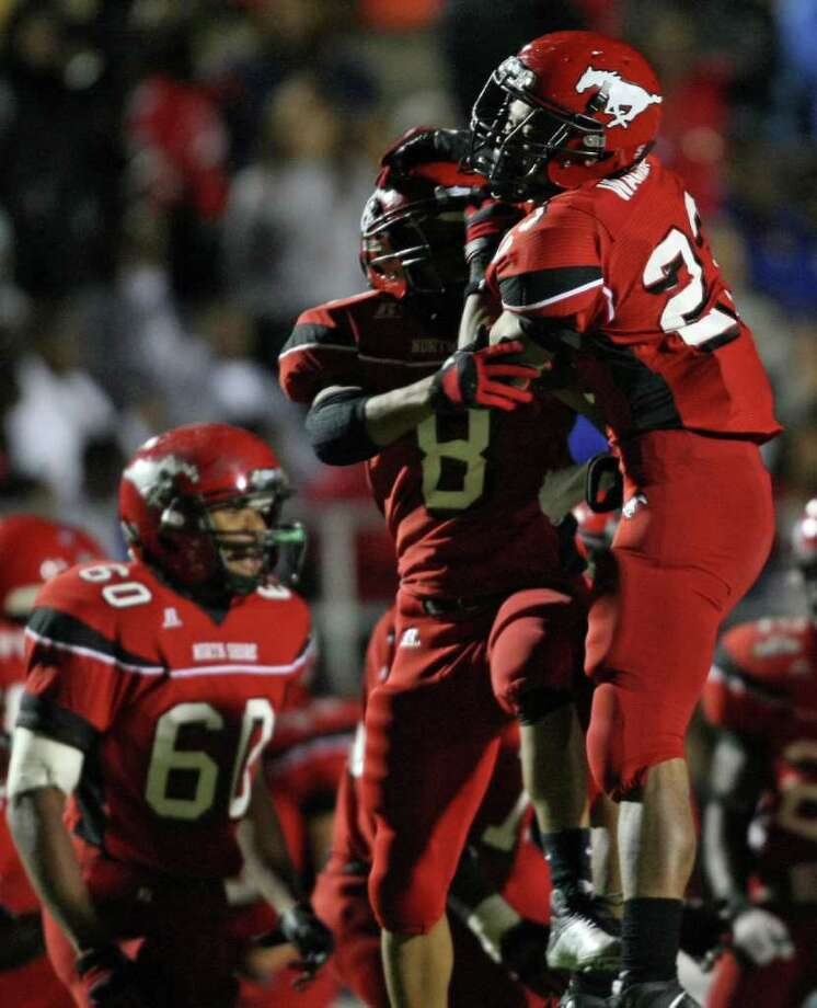 North Shore's Jacoby Walker (right) celebrates his interception with teammate Tim Broden during the first half of a District 21-5A high school football game against Channelview, Friday, November 4, 2011 at Galena Park Stadium in Houston. Photo: Eric Christian Smith, For The Chronicle