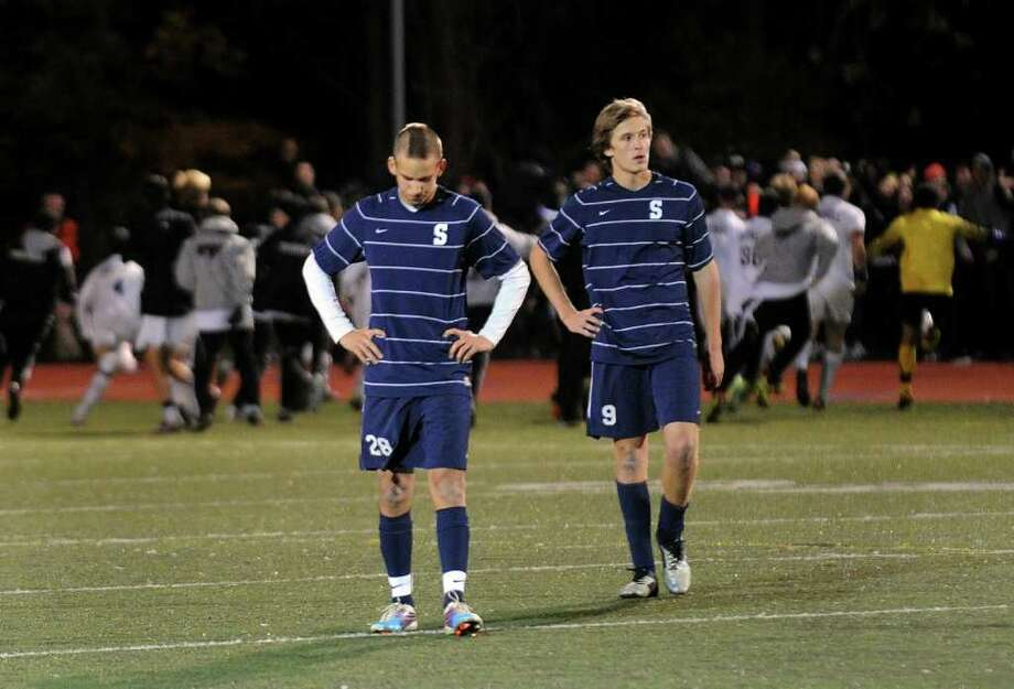 Staples' #28 Dylan Hoy and #9 Taylor McNair, right, walk off the field as Trumbull celebrates their win, during FCIAC Boys' Soccer Championship action in Fairfield, Conn. on Friday November 4, 2011. Photo: Christian Abraham / Connecticut Post