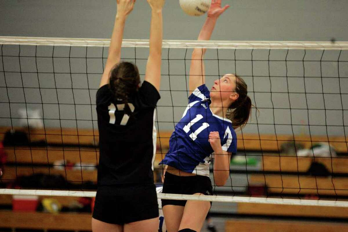 Darien High School volleyball player Katie Stueber spikes the ball while New Canaan's Isabelle Herde attempts to block during FCIAC playoff vollleyball action between the two squads. The # 1 seeded Blue Wave won in 3 sets to advance to the FCIAC finals. © J. Gregory Raymond