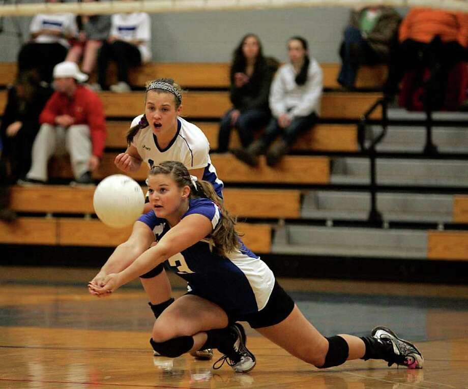 Darien senior volleyball player Charlett Stevenson lunges to make a bump pass while teammate Amanda Sommi looks on. The # 1 ranked Blue Wave bested the New Canaan squad to reach the FCIAC finals.  © J. Gregory Raymond Photo:  J. Gregory Raymond / Stamford Advocate