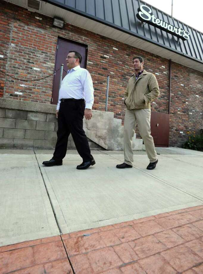 Troy Mayor Harry Tutunjian, left, and Tim Mattice of the community development office walk on a new sidewalk next to Stewarts in South Troy, N.Y. Friday, Nov. 4, 2011. The new sidewalks are part of a neighborhood revitalization project. (Lori Van Buren / Times Union) Photo: Lori Van Buren