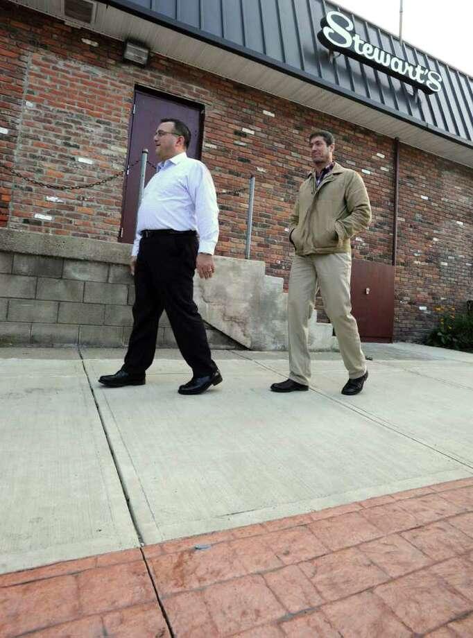 Troy Mayor Harry Tutunjian, left, and Tim Mattice of the community development office walk on a new sidewalk next to Stewarts in South Troy, N.Y. Friday, Nov. 4, 2011. The new sidewalks are part of a neighborhood revitalization project. (Lori Van Buren / Times Union) Photo: Lori Van Buren