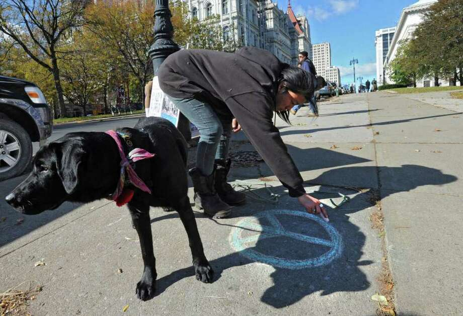Occupy Albany marcher Soojee Eckardt-Rigberg of Delmar holds her dog Obi as she draws a peace symbol on the sidewalk with chaulk before marching down State St. to Bank of America in Albany, N.Y. Friday, Nov. 4, 2011. The marchers were urging people to close their bank accounts at Bank of America and open an account with a credit union such as SEFCU. (Lori Van Buren / Times Union) Photo: Lori Van Buren
