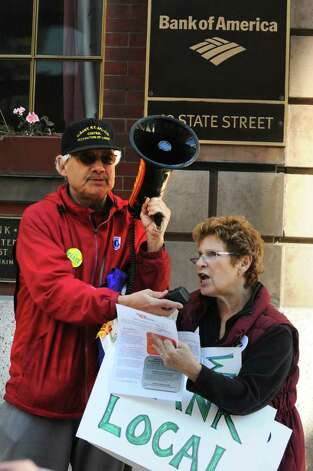 Occupy Albany marchers Doug Bullock and Susan Weber protest outside of the Bank of America on State St. in Albany, N.Y. Friday, Nov. 4, 2011. The marchers were urging people to close their bank accounts at Bank of America and open an account with a credit union such as SEFCU. (Lori Van Buren / Times Union) Photo: Lori Van Buren
