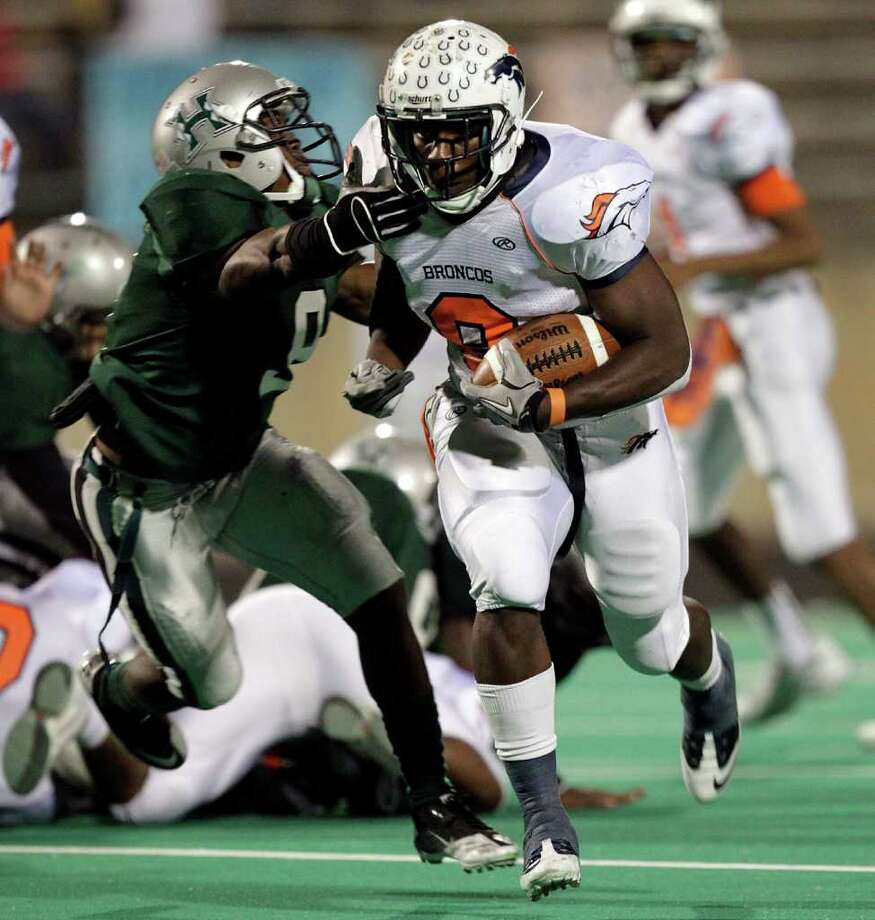 Bush running back Jalynn McCain #8 rushes past Hightower's Myles Houston #9 for a 30 yard score during the 23-5A district championship between Bush and Hightower Friday, November 4, 2011 in Missouri City, Texas. Photo: Bob Levey, Houston Chronicle / ©2011 Bob Levey