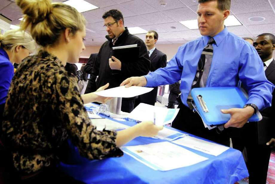 In this Nov. 2, 2011 photo, Clarence Turner of Little Canada, Minn., hands in his resume at the Minneapolis Career Fair held in Bloomington, Minn., where he was looking for a hotel audit job, preferably on the night shift, to help juggle family life with a baby. Hiring slowed in October as employers faced more uncertainty over future economic growth. (AP Photo/Jim Mone) Photo: Jim Mone / AP