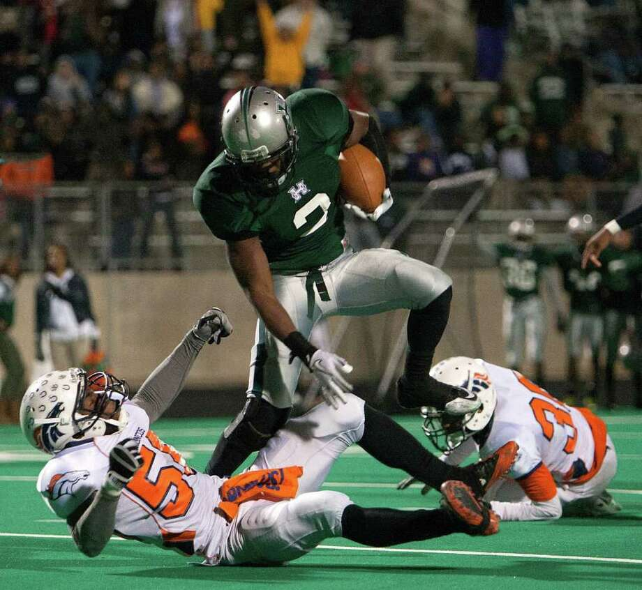 BOB LEVEY: FOR THE CHRONICLE GROUND AND POUND: Hightower's Joshua Wilhite, center, rolls over Bush linebacker Henry Offiah on his way to the game-winning score. Photo: Bob Levey / ©2011 Bob Levey