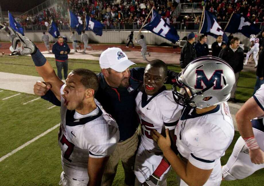 NICK de la TORRE: Chronicle THRILL OF VICTORY: Manvel coach Kirk Martin, in white cap sandwiched between Manuel Martinez (left) and Corey Seymour, relishes the District 24 4A championship and unbeaten season his team just ensured with a win over Dawson. Photo: Nick De La Torre / © 2011  Houston Chronicle