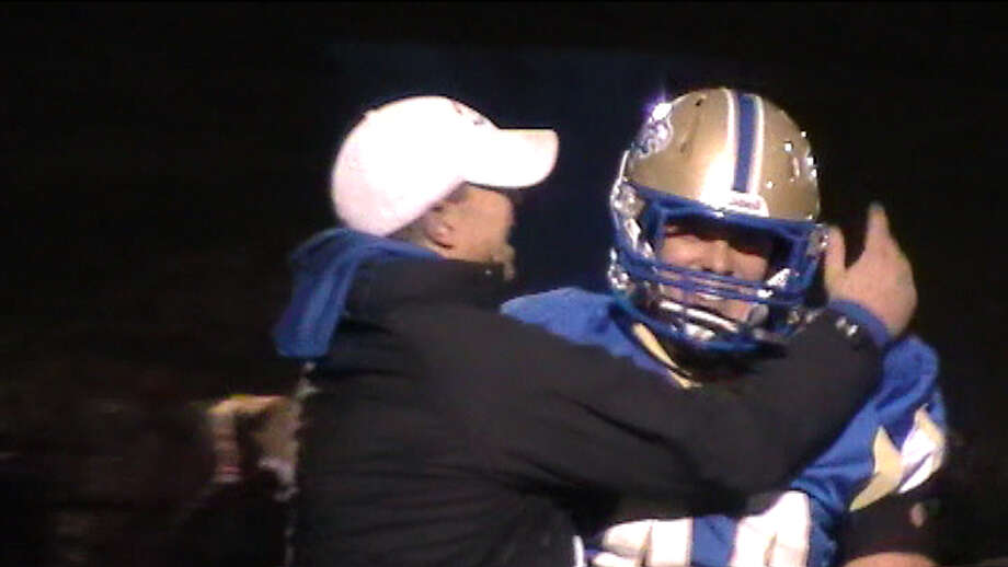 Newtown coach Steve George hugs senior back Lou Fenaroli for breaking the school's career rushing mark on the final play of Newtown's 33-7 victory over Bethel Friday, November 4, 2011. Photo: News-Times, Sean Patrick Bowley