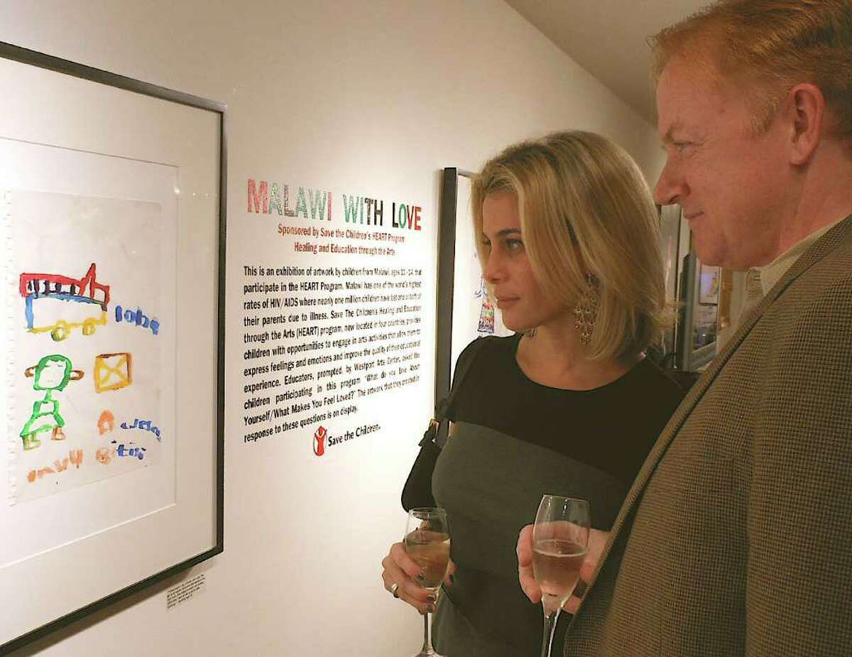 Randi and Sean McDonnell study a painting created by a young Malawian artist at Westport Arts Center exhibit.