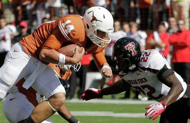 Texas quarterback David Ash (14) prepares to hit Texas Tech defender Jared Flannel (22) during the second quarter of an NCAA college football game, Saturday, Nov. 5, 2011, in Austin, Texas. (AP Photo/Eric Gay)