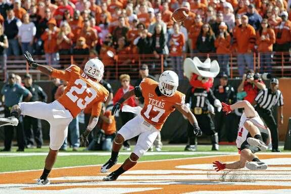 AUSTIN, TX - NOVEMBER 5: Cornerbacks Carrington Byndom #23 and Adrian Phillips #17 of the Texas Longhorns break up a first quarter touchdown pass to wide receiver Austin Zouzalik #6 of the Texas Tech Red Raiders on November 5, 2011 at Darrell K. Royal-Texas Memorial Stadium in Austin, Texas.