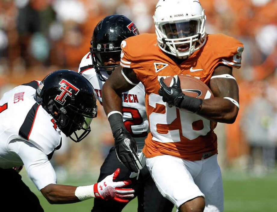 Texas' D.J. Monroe (26) runs past Texas Tech defenders Derrick Mays, left, and  Jared Flannel, center, during the second quarter of an NCAA college football game, Saturday, Nov. 5, 2011, in Austin, Texas. (AP Photo/Eric Gay) Photo: Eric Gay, Associated Press / AP