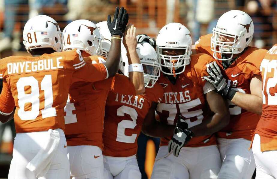 Texas' Fozzy Whittaker (2) celebrates with teammates after he scored during the second quarter of an