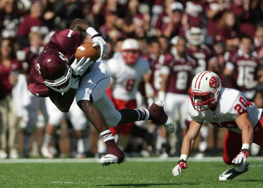 James Rhoden of Cinco Ranch High School looses his footing after catching a pass as Drake Dowling of Katy High School chases him during the second quarter of a high school footbal game, Saturday, Nov. 5, 2011, at Rhodes Stadiumin Katy. Photo: Nick De La Torre, Houston Chronicle / © 2011  Houston Chronicle