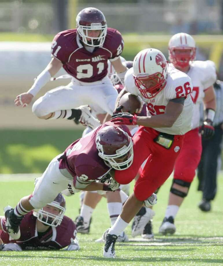 Rodney Anderson of Katy High School, (26) tries to break away from Tony Castillo and the Cinco Ranch High School defense during the second quarter of a high school footbal game, Saturday, Nov. 5, 2011, at Rhodes Stadiumin Katy. Photo: Nick De La Torre, Houston Chronicle / © 2011  Houston Chronicle