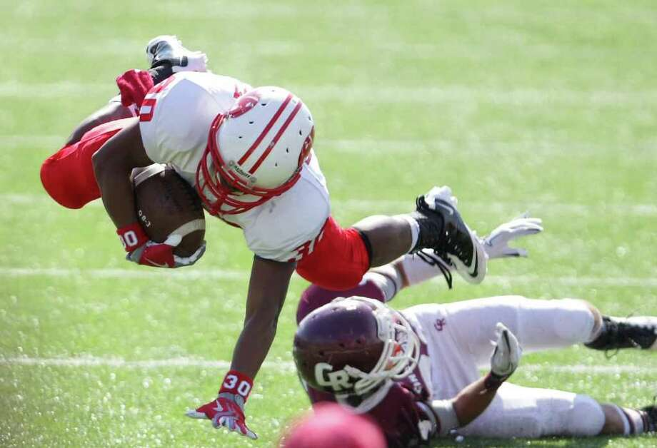 Ricky Bickham of Katy High School, top, dives over Tony Castillo of Cinco Ranch High School for a touchdown during the third quarter of a high school football game, Saturday, Nov. 5, 2011, at Rhodes Stadium in Katy. Katy High School won 38-7. Photo: Nick De La Torre, Houston Chronicle / © 2011  Houston Chronicle
