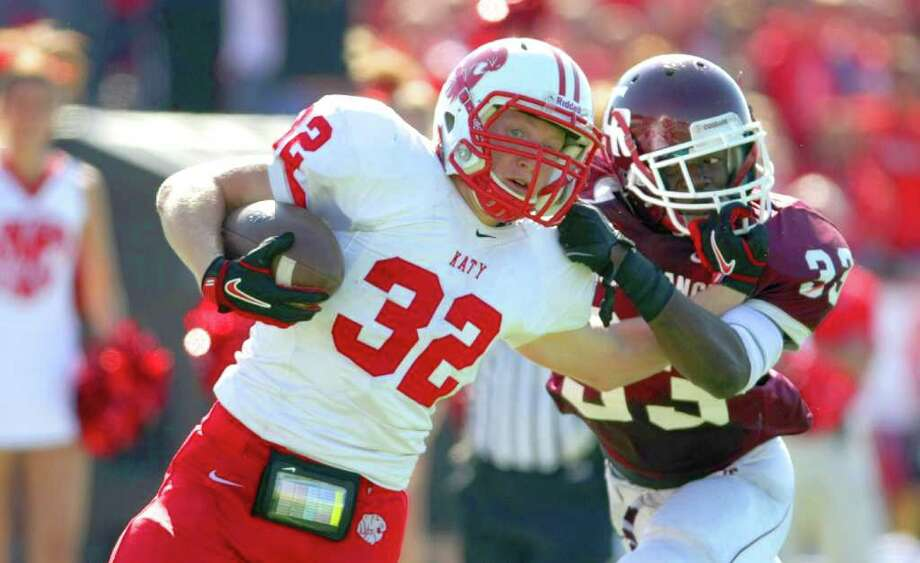 Cody Gomez, of Katy High School, left fights to get by Ayodele Ilesanmi of Cinco Ranch High School during the second quarter of a high school game, Saturday, Nov. 5, 2011, at Rhodes Stadium in Katy. Photo: Nick De La Torre, Houston Chronicle / © 2011  Houston Chronicle