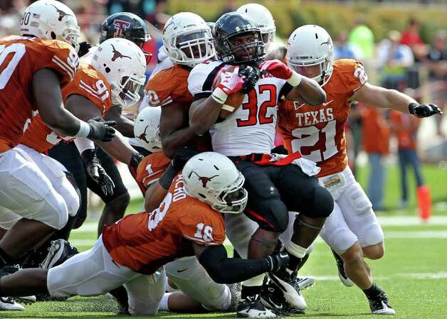 Red Raider running back Aaron Crawford is stopped at the line by a swarming UT defense in the fourth quarter as Texas plays Texas Tech at Royal Stadium on November 5, 2011.  Tom Reel/Staff Photo: TOM REEL, E / © 2011 San Antonio Express-News