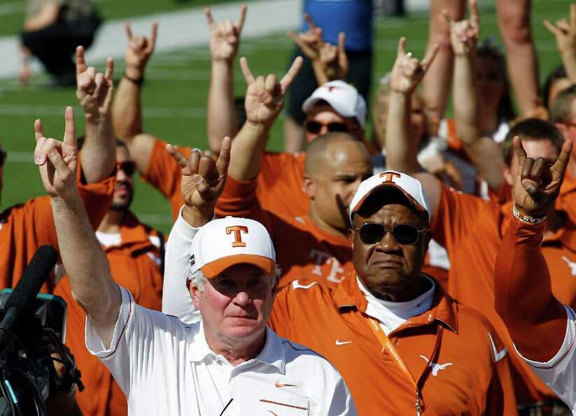 Texas coach Mack Brown, front left, takes part in the school song following an NCAA college football