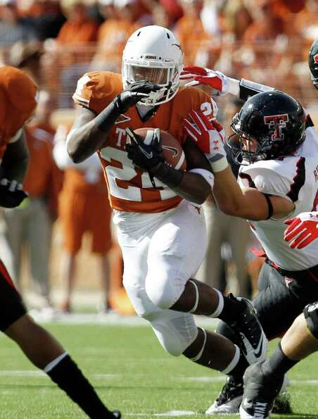 Texas' Joe Bergeron (24) runs up the middle as Texas Tech's Jackson Richards defends during the firs