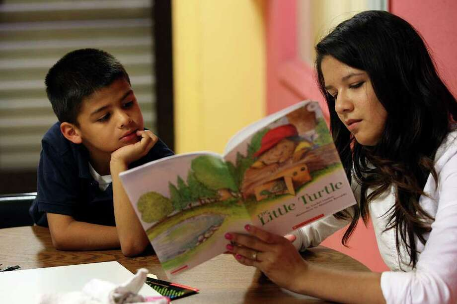 Brooke Small, 19, tutors Jacob Mora, 8, during the SAReads program at the Dan Cook Youth Center. Photo: JERRY LARA, San Antonio Express-News / SAN ANTONIO EXPRESS-NEWS