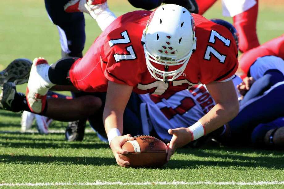 Offensive Lineman, Damian Orellano of the Greenwich Cardinals recovers a fumble in the first half of play as the Greenwich Cardinals Varsity Football Team play the Brien McMahan Senators on Saturday, November 5th in Greenwich, Conn. Photo: David E. Johnston