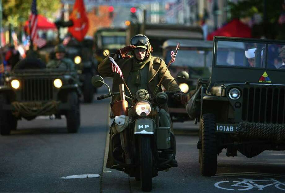 A participant on a vintage military motorcycle salutes during the regional Auburn Veterans Day Parade. Photo: JOSHUA TRUJILLO / SEATTLEPI.COM