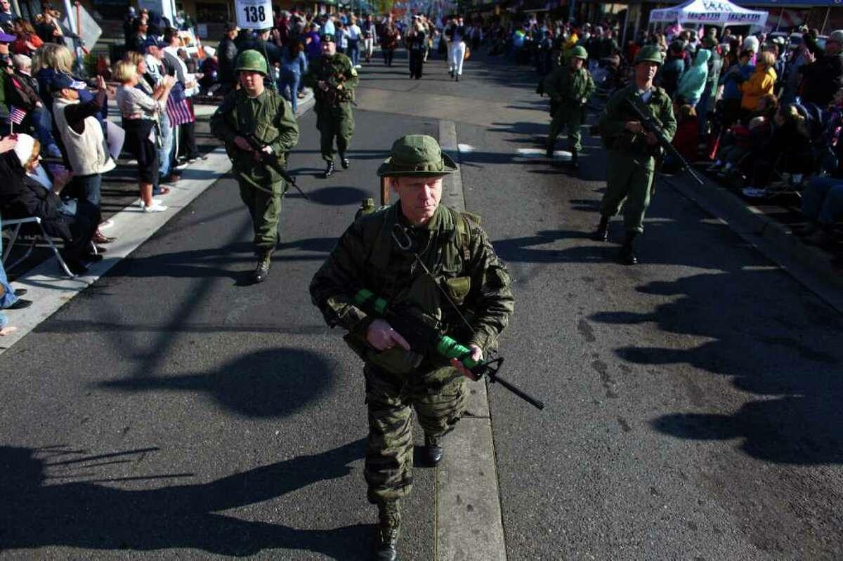 Participants in Vietnam War-era uniforms march during the regional Auburn Veterans Day Parade.