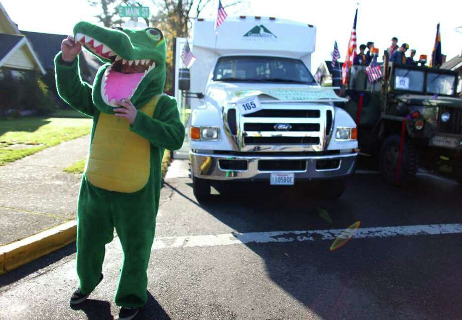 Joseph Dombrowski, part of the Green River Community College entry, peeks from his school mascot costume. Photo: JOSHUA TRUJILLO / SEATTLEPI.COM