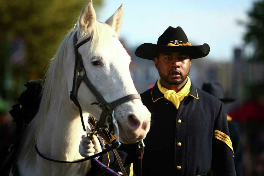 Geordan Newbill of the Buffalo Soldiers of Seattle marches with Misty during the regional Auburn Veterans Day Parade. Photo: JOSHUA TRUJILLO / SEATTLEPI.COM