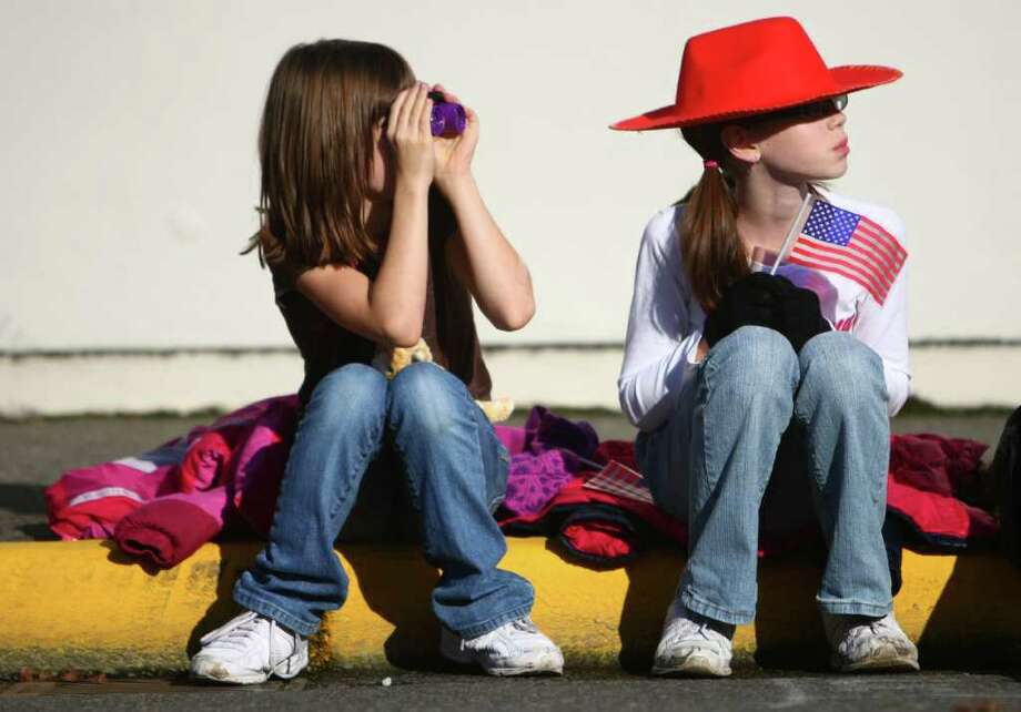 Jasmin Nicholson, 8, and Jada Nicholson, 10, watch the regional Auburn Veterans Day Parade. Photo: JOSHUA TRUJILLO / SEATTLEPI.COM