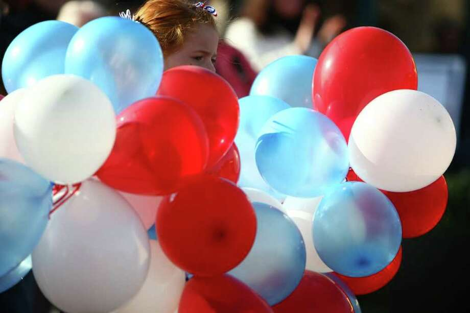 A member of the Auburn Dance Academy holds onto balloons during the regional Auburn Veterans Day Parade on Saturday in downtown Auburn. The parade, billed as the largest Veterans Day parade west of the Mississippi, has been held in the King County town for 46 years. Photo: JOSHUA TRUJILLO / SEATTLEPI.COM