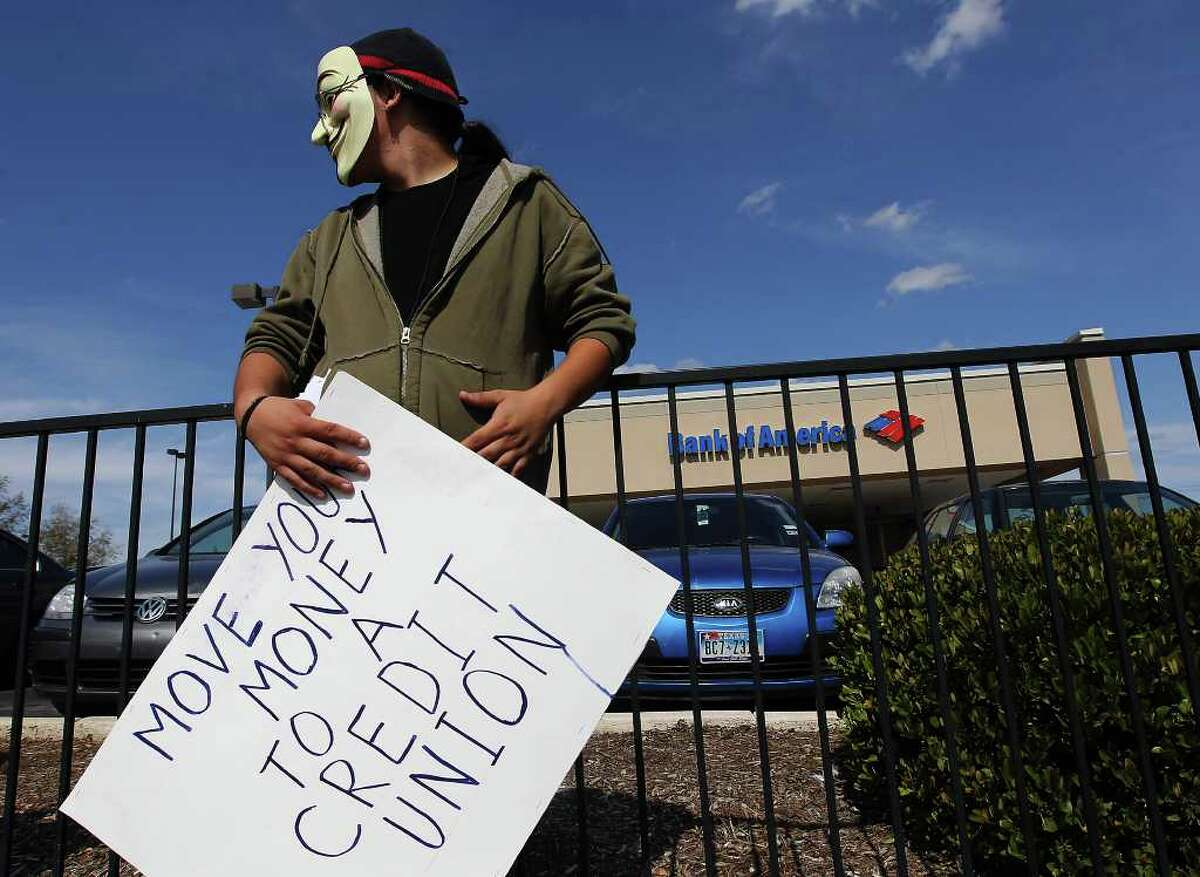 An Occupy San Antonio activist stands near a Bank of America branch office off Vance Jackson during a recent protest in conjunction with members of MoveOn.org San Antonio on Saturday, Nov. 5, 2011. Later, the Occupy SA group marched in the downtown area. Kin Man Hui/kmhui@express-news.net