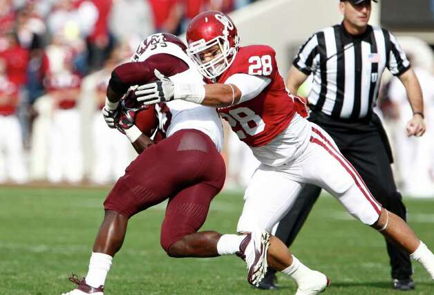 Oklahoma linebacker Travis Lewis (28) tackles Texas A&M running back Christine Michael (33) during the first quarter of an NCAA college football game in Norman, Okla. on Saturday, Nov. 5, 2011. Photo: AP