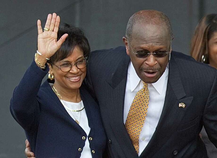 FILE - In this May 21, 2011, file photo, Gloria Cain, left, accompanies her husband Herman Cain as he announces his run as a Republican candidate for president in Atlanta. Gloria Cain is hardly the traditional presidential campaign wife.  She has been virtually absent from the campaign trail as her husband runs for the Republican presidential nomination. And she?s been silent as he fights to overcome allegations that he sexually harassed women while he led the National Restaurant Association in the 1990s. (AP Photo/David Goldman, File) Photo: David Goldman / AP