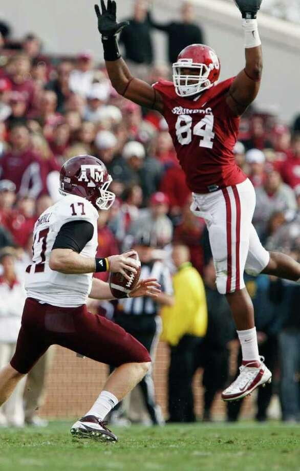 Texas A&M  quarterback Ryan Tannehill (17) scrambles as Oklahoma defensive end Frank Alexander (84) attempts to block his pass in the second quarter of an NCAA college football game in Norman, Okla. on Saturday, Nov. 5, 2011.  (AP Photo/Alonzo J. Adams) Photo: Alonzo Adams, Associated Press / FR159426 AP