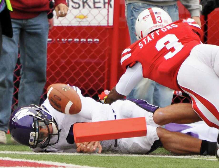 DAVE WEAVER: ASSOCIATED PRESS PILING ON: Kain Colter gets past Nebraska's Daimion Stafford for one of the Northwestern quarterback's two rushing touchdowns. Photo: Dave Weaver