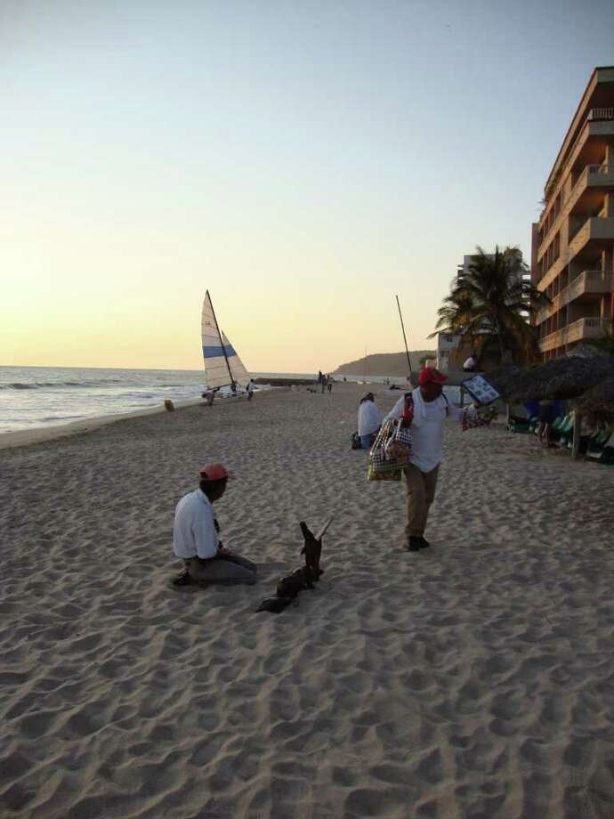 DUDLEY ALTHAUS : CHRONICLE SLOW: Vendors scrounge for sales on a near empty beach in Mazatlan's Golden Zone. While still the off season, vendors and visitors say the beach is far quieter than in the past. Photo: Dudley Althaus
